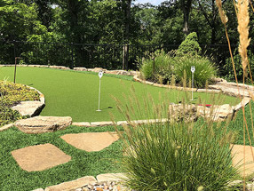 putting green made of artificial turf, edged with Flagstone and weathered boulders