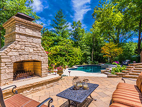 outdoor fireplace, patio and pool in a woodland garden
